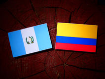 Guatemalan flag with Colombian flag on a tree stump isolated Royalty Free Stock Image