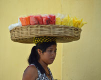 Guatemalan lady selling fruit (1). ANTIGUA, GUATEMALA - JUNE 27, 2015; An unknown, young Guatemalan woman carries sliced fruit in a basket on her head. She walks royalty free stock image