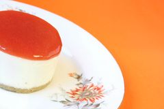 Guava Cheesecake. A portion of guava cheesecake on a white floral plate over a bright orange background, with selective focus and copy-space. Guava is used in stock photos