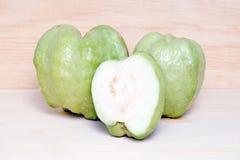 Guava fruit and half piece isolated on wood background. Guava fruit Also called as, Psidium guajava, lemon guava, guayaba, Arawak guayabo, Subergine, common Royalty Free Stock Photography