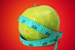 Guava with measuring tape. Half guava with measuring tape ,healthy concept stock image