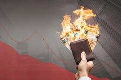 Gubienie pieniądze pojęcie - palić euro rachunki przed opadającym wykresem fotografia royalty free