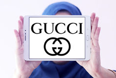 Gucci logo. Logo of fashion company gucci on samsung tablet holded by arab muslim woman stock photo