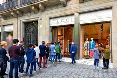 Gucci store in Barcelona, Spain. Barcelona, Spain - May 5, 2018:  People wait in line to enter the Gucci, the Italian luxury brand store on Passeig de Gràcia Royalty Free Stock Photo