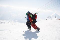 Gudauri, Georgia - 6 de marzo de 2017 Paragliding del invierno en las montañas del Cáucaso sobre altos picos y el valle Imagen de archivo libre de regalías