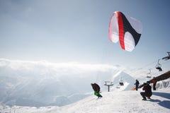 Gudauri, Georgia - 6 de marzo de 2017 Paragliding del invierno en las montañas del Cáucaso sobre altos picos y el valle Imágenes de archivo libres de regalías
