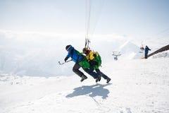 Gudauri, Georgia - 6 de marzo de 2017 Paragliding del invierno en las montañas del Cáucaso sobre altos picos y el valle Fotografía de archivo
