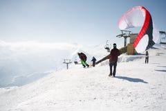 Gudauri, Georgia - 6 marzo 2017 Parapendio di inverno in montagne di Caucaso sopra gli alti picchi e la valle Fotografia Stock