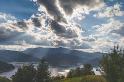 Guden rays ovanför en sjö på foten av ett berg och fördunklar på himlen Arkivfoton