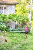 GUDEVITSA,保加利亚- 2017年7月22日:未认出的老妇人吃草她的母鸡坐在一个农村房子前面的一条长凳 免版税库存照片