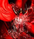 Gudinna av förälskelse i röd klänning med storartat hår och hjärtor arkivfoto