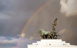 GudinnaVictoria ridning på quadrigaen (altaret av fäderneslandet) mot bakgrunden av stormig himmel och regnbågen Royaltyfri Foto