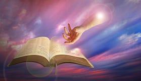 Gudomlig hand av guden med bibeln Arkivbilder