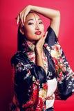 Gueixa bonita nova no fundo vermelho que levanta no quimono, oriental Imagem de Stock Royalty Free
