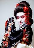Gueixa bonita nova no quimono preto entre sakura, cl asiático do ethno fotos de stock royalty free