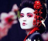 Gueixa consideravelmente real dos jovens no quimono com sakura e decoração sobre fotos de stock