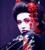 Gueixa consideravelmente real dos jovens no quimono com sakura e decoração sobre foto de stock royalty free