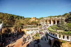 Guell park in Barcelona. BARCELONA, SPAIN - August 17, 2017: View on the Dragon stairway and terrace with tourists in Guell park, famous public park with gardens Stock Image