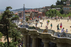 Guell Park Barcelona Catalunia Spain. The curved ceramic blue and white tile benches and a tower of a building of Guell Park. Barcelona, Catalunia, Spain stock photography