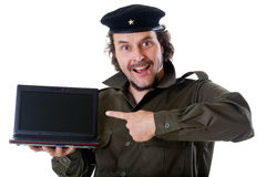 Guerilla with a net book. Mid-aged man in authentic 1950s/60s military uniform shirt and beret hat, holding a netbook and pointing to the screen Stock Photos