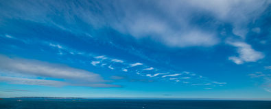 Guernsey cloud skyline. Guernsey island horizon sky photo with clouds and airplane exhaust Stock Images