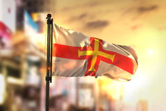 Guernsey Flag Against City Blurred Background At Sunrise Backlig Royalty Free Stock Photos