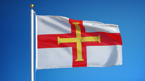 Guernsey flag in slow motion seamlessly looped with alpha. Guernsey flag waving in slow motion against clean blue sky, seamlessly looped, close up, isolated on stock video footage