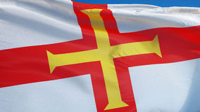 Guernsey flag in slow motion seamlessly looped with alpha. Guernsey flag waving in slow motion against clean blue sky, seamlessly looped, close up, isolated on stock footage