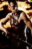 Guerreiro antigo de Roma com a espada no fundo do fogo imagens de stock royalty free