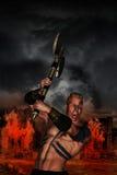 Guerreiro bárbaro com vila flamejante Fotos de Stock