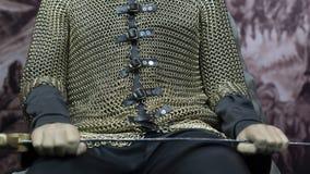 Guerreiro corajoso que guarda seus espada e protetor e que senta-se no trono fotos de stock royalty free