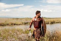 Guerrero antiguo que lucha en fondo del paisaje Imagen de archivo