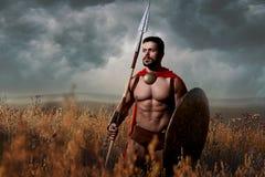 Guerrero con la espada y el escudo que entran en ataque imagenes de archivo