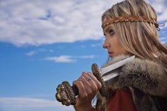 Guerrero de la muchacha de Vikingo en un fondo del cielo azul imágenes de archivo libres de regalías