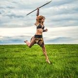 Guerrero de la muchacha en el campo Salte con una lanza Foto de archivo libre de regalías