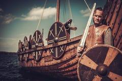 Guerrero de Viking con la espada y el escudo que se colocan cerca de Drakkar en la costa Imagen de archivo libre de regalías