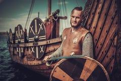 Guerrero de Viking con la espada y el escudo que se colocan cerca de Drakkar en la costa Fotos de archivo