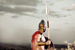 Guerrero espartano fuerte en vestido de batalla con un escudo y una lanza Imágenes de archivo libres de regalías