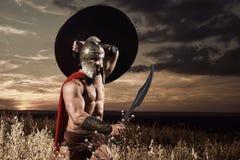 Guerrero espartano que entra adelante en ataque con la espada Imagen de archivo libre de regalías
