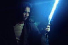 Guerrero joven que lleva a cabo un lightsaber Fotografía de archivo libre de regalías