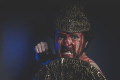 Guerrero medieval, barbudo del hombre con el casco del metal y escudo, salvaje Imagenes de archivo