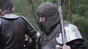 Guerrero medieval en armadura del chainmail con un hacha, en el bosque debajo de la lluvia almacen de video
