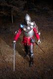 Guerrero medieval en el traje del caballero que se coloca en Forest Ready oscuro para la batalla, tiro integral Imagen de archivo libre de regalías