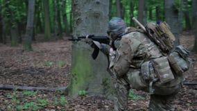 Guerrero parcial de la guerrilla que apunta en la emboscada del bosque que lleva su arma metrajes