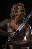 Guerrero picto que lame una espada, cubierta en fango y desnuda Imagen de archivo