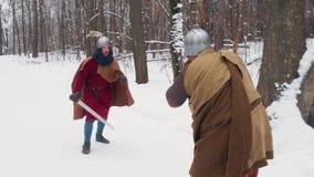 Guerreros irlandeses y frankish medievales en armadura que luchan en un bosque del invierno con las espadas y los escudos almacen de video