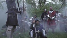 Guerreros medievales despu?s de la batalla en el bosque, con las armas en humo metrajes