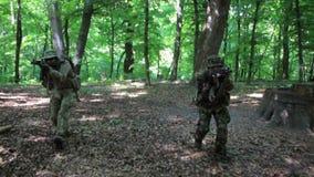 Guerreros parciales de la guerrilla que atacan apuntar en la emboscada del bosque que lleva sus armas El campo de batalla de la g almacen de metraje de vídeo