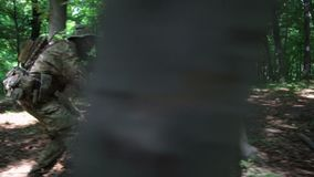 Guerreros parciales de la guerrilla que atacan apuntar en la emboscada del bosque que lleva sus armas El campo de batalla de la g almacen de video