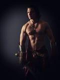 Guerrier à moitié nu avec une épée dans des vêtements médiévaux images stock
